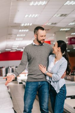 smiling couple choosing mattress together in furniture shop