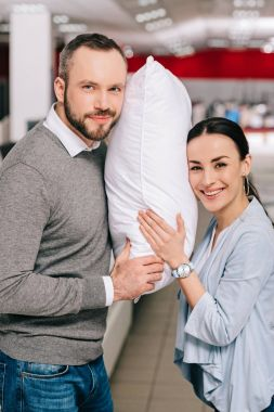 portrait of smiling couple with pillow in furniture store