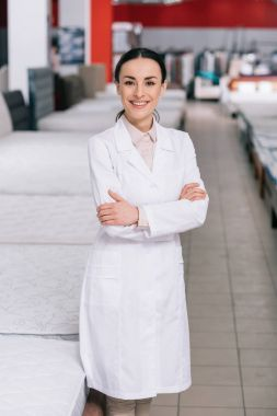 portrait of smiling shop assistant in white coat with arms crossed in furniture shop with arranged mattresses