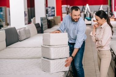 couple with folding mattresses in furniture store with arranged mattresses