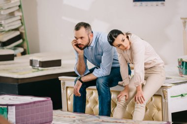 portrait of bored couple in furniture store with arranged mattresses