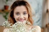 gazdaság, fehér virágok, és mosolyogva kamera a gyönyörű fiatal nő portréja
