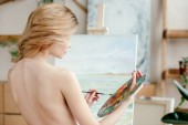 back view of naked young artist holding brush and palette in art studio