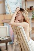 Seitenansicht des sinnlichen nackten Künstler mit geschlossenen Augen an Bild auf Staffelei gelehnt