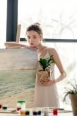 Fényképek gyönyörű fiatal nő festő gazdaság cserepes növény, és támaszkodva a festőállvány a művészeti stúdió