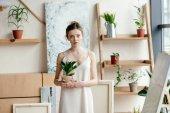 gyönyörű fiatal nő gazdaság cserepes növény és látszó-on fényképezőgép, művészeti stúdió