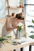 Fényképek gyönyörű fiatal nő szippantás a virágok locsolókanna művészeti stúdió