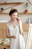 Fényképek gyönyörű, fiatal festő üzem ecset mosolyogva miközben beszél a smartphone és látszó-on festőállvány művészeti stúdió