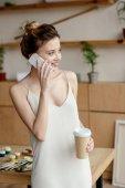 Fényképek szép mosolygó fiatal nő gazdaság kávé, hogy menjen, és beszél a smartphone művészeti stúdió