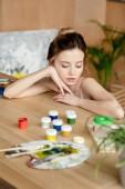 Fényképek gyönyörű pályázat fiatal művész ferde asztalhoz a festékek és a paletta