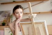 Fényképek gyönyörű töprengő fiatal művész támaszkodva a festőállvány, és keres el