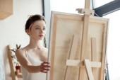 Fényképek gyönyörű fiatal művész látszó-on kép-festőállvány