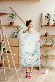 Fotografie voller Länge Blick auf schöne junge nackte Künstlerin in roten Sandalen Bild halten und wegschauen im studio