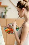 Fényképek oldalnézet vonzó fiatal művész a paletta és ecset festés a festőállvány a stúdió