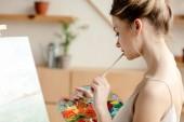 Fényképek a vonzó női festő gazdaság paletta és ecset, művészeti stúdió oldalnézete