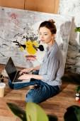 Fényképek szép fiatal női előadó használ laptop-val üres képernyő a stúdió