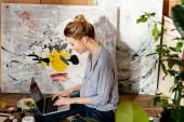 Fényképek mosolygó fiatal nő festő használ laptop művészeti stúdió oldalnézetből