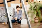 Fényképek szelektív összpontosít gyönyörű fiatal művész gazdaság kávét, megy és használ laptop stúdió