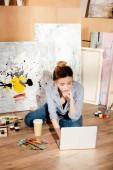 Fényképek gyönyörű fiatal művész használ laptop művészeti stúdió
