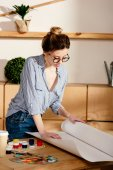 stylish female artist in eyeglasses rolling canvas on table with painting supplies
