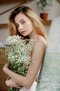 beautiful tender girl holding white flowers and looking at camera in art studio