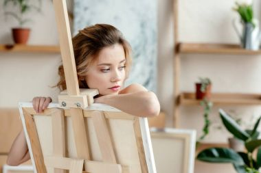 beautiful sensual young woman leaning at easel and looking away in art studio