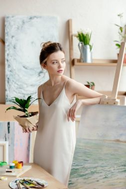 beautiful young artist with green potted plant leaning at picture on easel and looking away in art studio