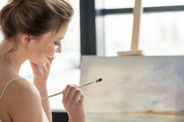 beautiful smiling young woman holding brush and looking down in art studio