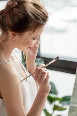 beautiful smiling young painter holding brush and talking by smartphone in art studio
