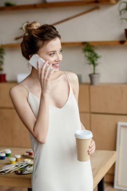 beautiful smiling young woman holding coffee to go and talking by smartphone in art studio