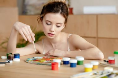 beautiful young female painter holding brush and looking at palette in art studio