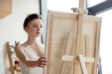 beautiful young artist looking at picture on easel