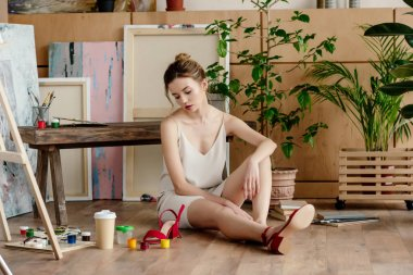 frustrated young female artist sitting on floor in studio
