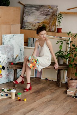 beautiful elegant young artist holding palette and looking away in studio