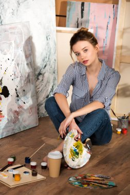 beautiful young artist sitting on floor and looking at camera in art studio