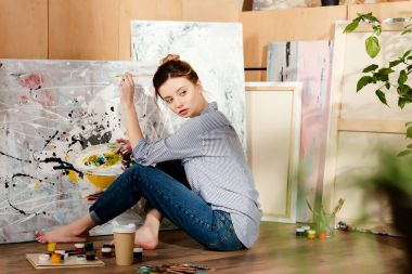 beautiful young barefoot artist sitting on floor and painting picture in studio