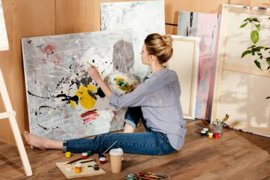 beautiful young female painter sitting on floor and drawing picture in art studio
