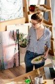 Fotografie stilvolle Künstlerin in Brillen halten Pflanze und Palette im studio