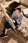 magas szög kilátás elegáns női előadó a festőállvány festés szemüvegek