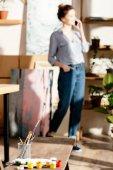 Fotografie Malerei liefert auf Bank und Künstlerin am Smartphone hinter sprechen