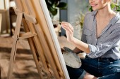 cropped image of young female artist painting on easel