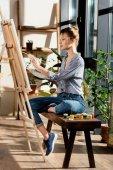 Fotografie Seitenansicht der Künstlerin sitzen auf Bank mit Farben und Zeichnung Bild auf Staffelei