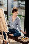 female artist sitting on bench with paints and drawing picture on easel