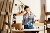 Fotografie Junge weibliche Künstler mit Pinsel und Malerei zu betrachten