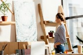 female artist with paintbrush behind ear looking at own picture in studio