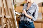 Fotografie Bild der jungen Frau mit Palette und Pinsel in Studio beschnitten