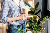 ořízne obraz mladé ženy s kávou dotýká Hrnková rostlina