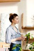 boční pohled na mladou ženu s šálkem kávy v ruce
