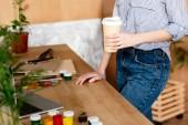 Oříznout obrázek ženské umělce s šálek kávy stojí u stolu s notebookem a malířské potřeby