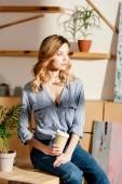 mladý atraktivní zpěvačkou papíru šálek kávy sedí na stole ve studiu